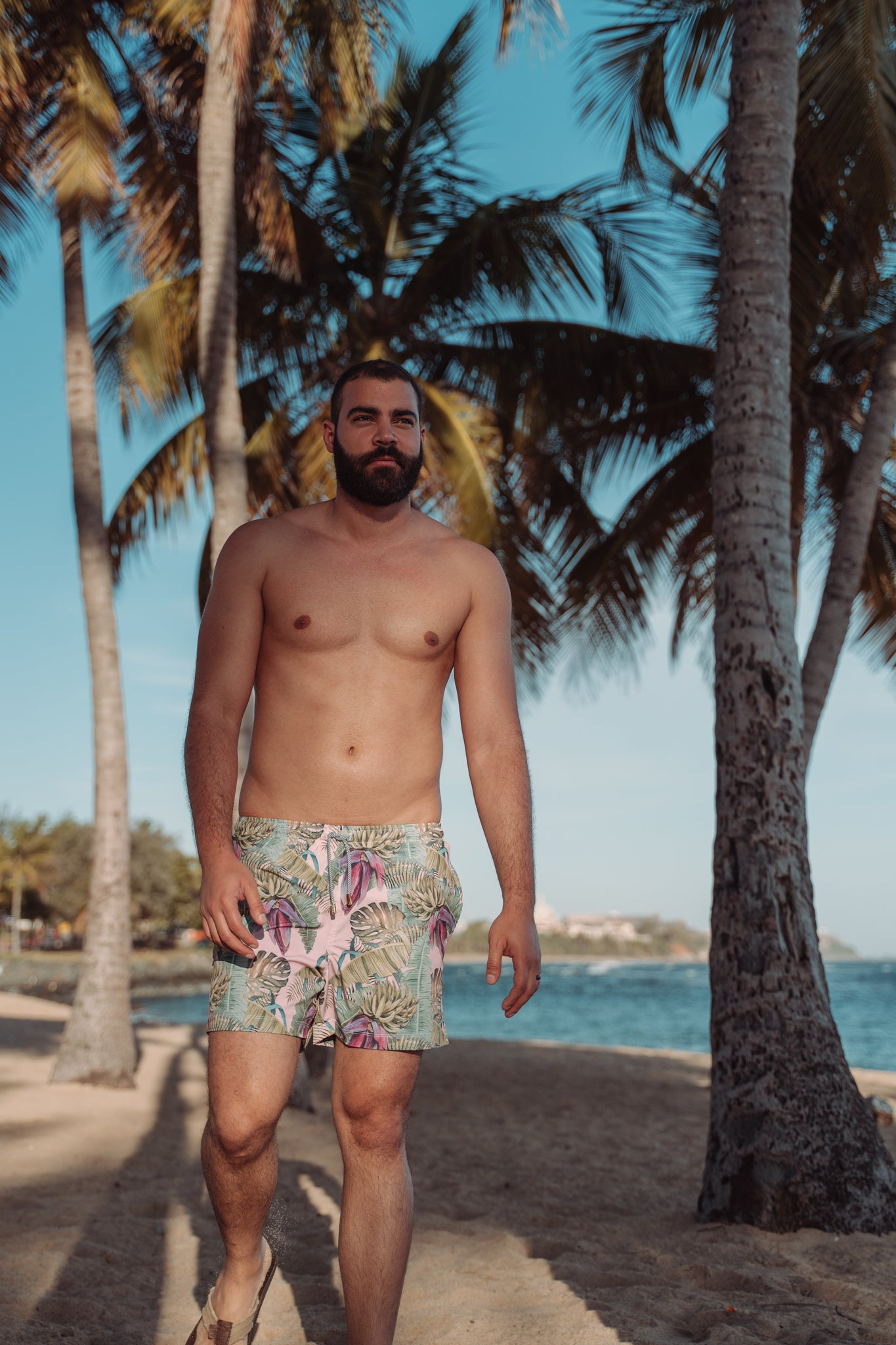 Male model shirtless walking in front of palm trees wearing amazing swim trunk