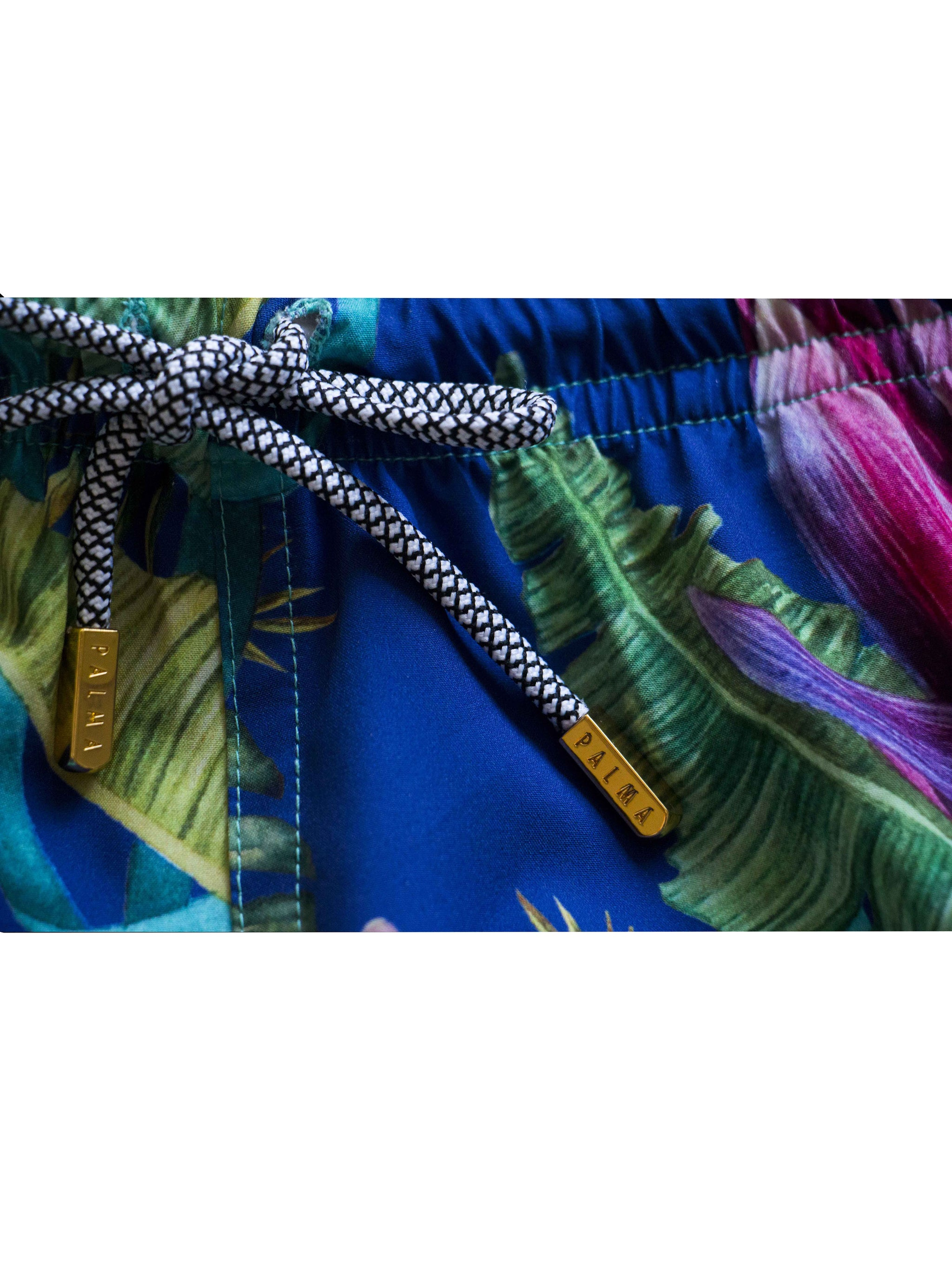 Close up of a sustainable swim trunk cord tie with luxury gold aglets with the word Palma