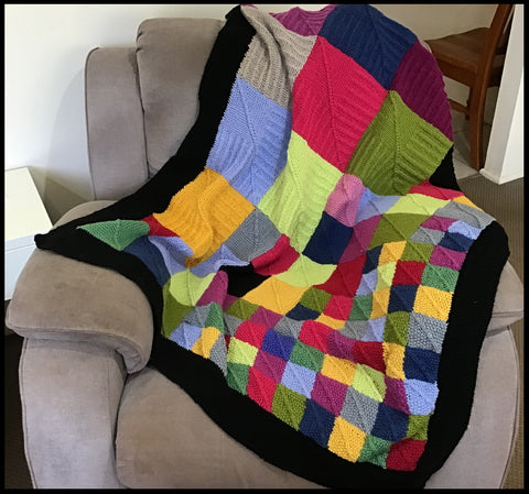 Tessellations hand knitted blanket with lovely stitches, colours using three different sized bkocks.