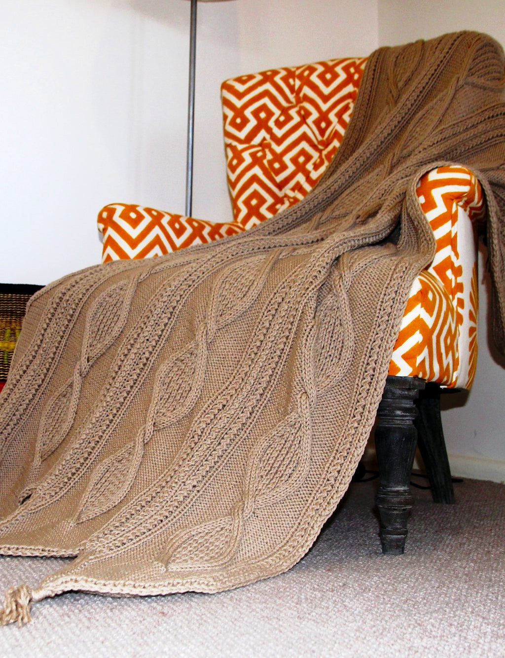 Knitted rug pattern using Almond Shell cables. Rug displayed draped over chair.