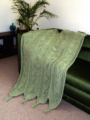 Unique knitted blanket with diamond cable and bobble pattern draped over satin covered chair.