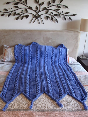 Beautiful warm, hand knitted blanket featuring chunky cable knit panels in blue displayed on a bed.