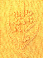Load image into Gallery viewer, Knitted bobble blossoms and twisted stitch leaves shown in close up.