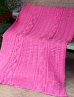 Load image into Gallery viewer, Hand knitted wool blanket featuring long panels of textured climbing leaf stitches. The blanket is pink and draped over a chair.
