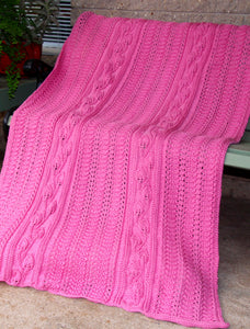 Hand knitted wool blanket featuring long panels of textured climbing leaf stitches. The blanket is pink and draped over a chair.