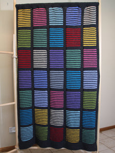 Easy knit blanket with coloured louvre style squares and solid colour burders hanging on a blanket display frame.
