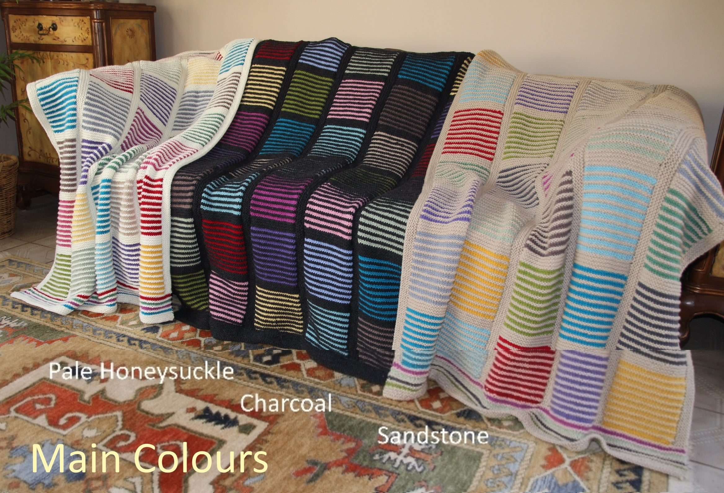 Easy knit woolen blanket in three colorways draped over chairs.