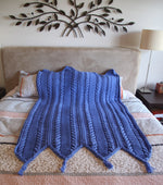Beautiful warm, hand knitted blue coloured blanket featuring chunky cable knit panels spread out on a bed.