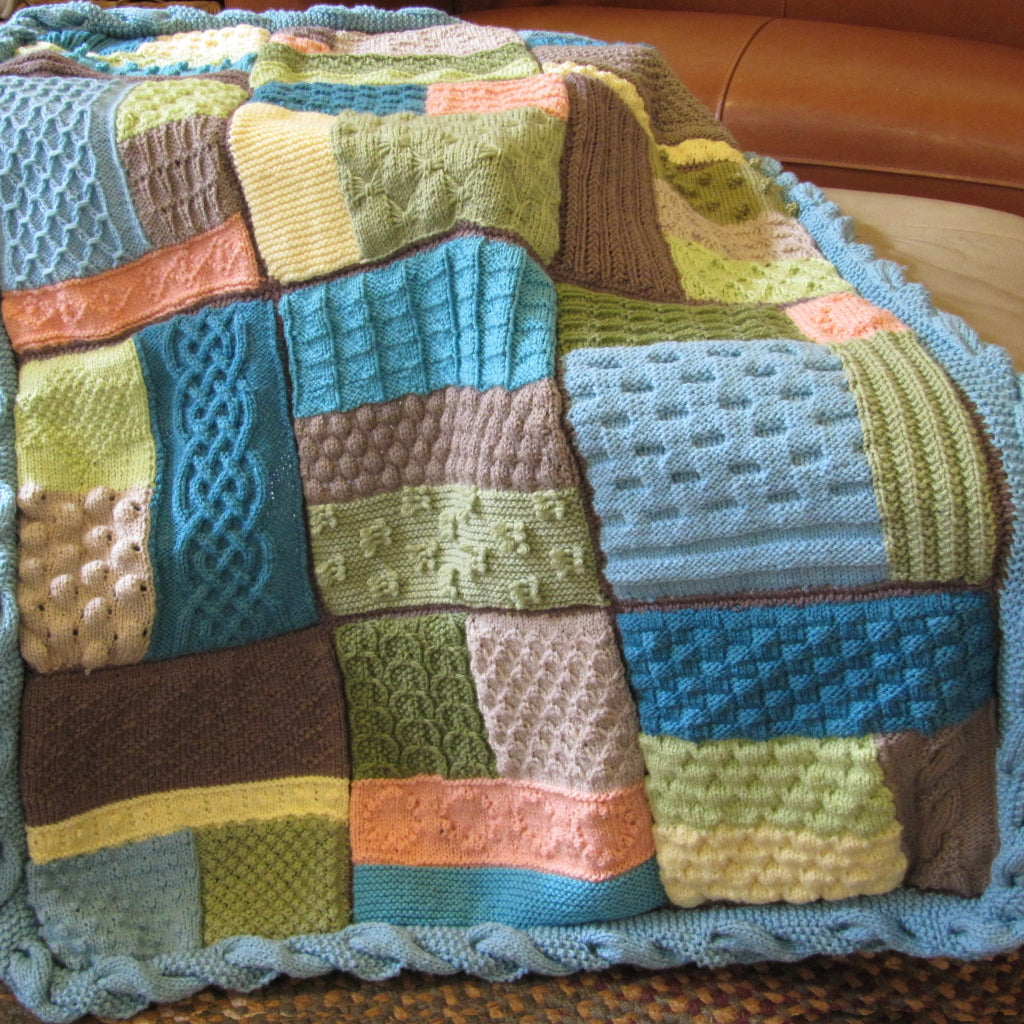 The Textured Sampler Blanket with cable twist edging draped over a chair