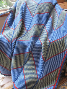 Hand knitted woolen blanket of joined panels. Each panel has diagonal wide bands in grey and blue. The complete blanket features horizontal zig-zags. Blanket displayed draped over a chair.