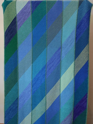 Hand-knitted woolen blanket, knitted in panels with diagonal rows. Complete blanket has both diagonal and vertical intermixed blue and green colours.