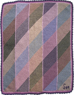 Hand-knitted woolen blanket, knitted in panels with diagonal rows. Complete blanket has both diagonal and vertical intermixed pastel colours.