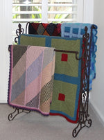 Load image into Gallery viewer, Four easy knit hand-knitted woolen blankets draped over a metal display stand.