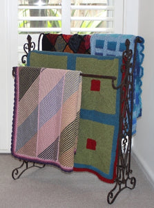 Four easy knit hand-knitted woolen blankets draped over a metal display stand.
