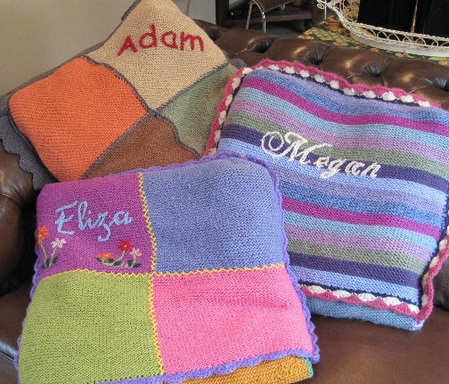 Three hand knitted woolen blankets folded into pillow pocket. Displayed arranged on a leather arm chair.
