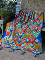 Knitted rug using multi-colours and diamond pattern. Rug displayed draped over chair to display edge tassels.