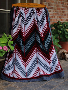 Hand knitted woolen blanket of joined panels. Each panel has diagonal wide bands in grey, red, white and black. The complete blanket features dramatic horizontal zig-zags.