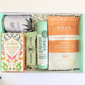 Koja protein pancakes, Naked Paleo snack bar, Pukka herbal tea, Nakula coconut water and Smoothie bombs perfect healthy nourishing gift box for recovery from illness.