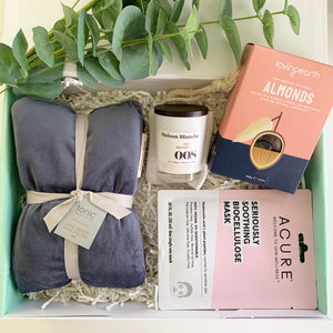 Gift box from Wishing You Well it includes: Luxe velvet heat pillow, Tonic Australia Chocolate coated almonds, Loving Earth Mini candle, Maison Blanche Face sheet mask or under eye hydrogels Acure Gift box with personalised gift card.