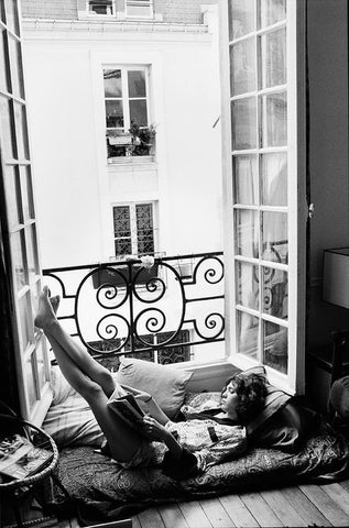 Black and White photography. Woman reading on balcony. Big open Windows