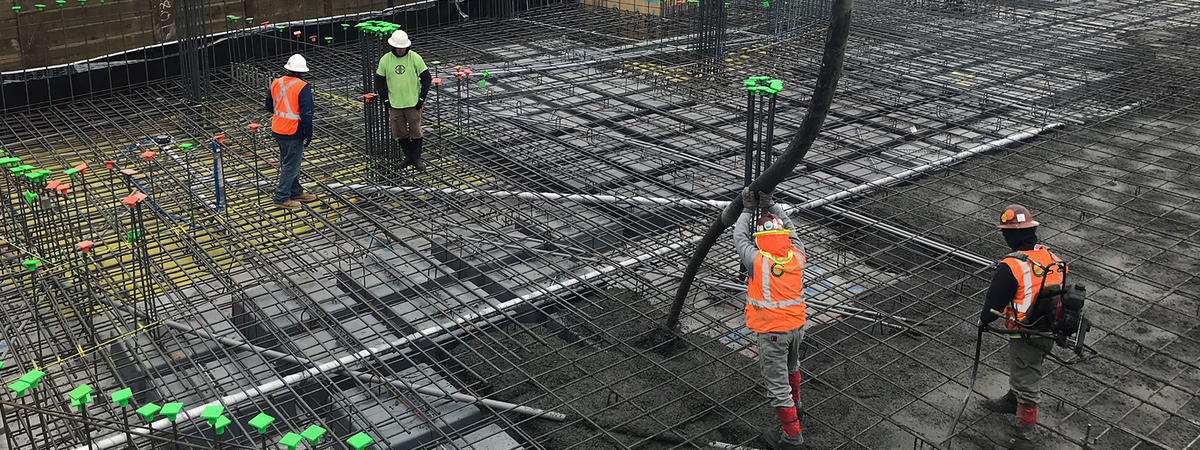 Construction crew standing on rebar over wafflemat boxes pouring concrete onto the waffle slab construction