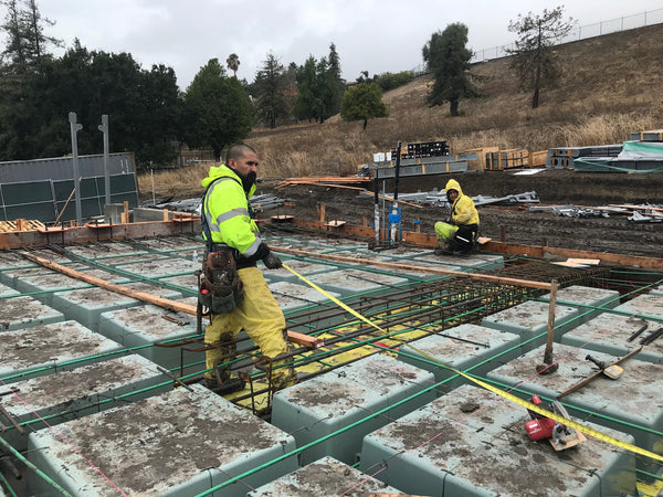 Workers for RJ Doston continue building the Wafflemat Foundation with perfect cable placement despite the rain. Process cycle time reduction is only one benefit of this incredible foundation system.