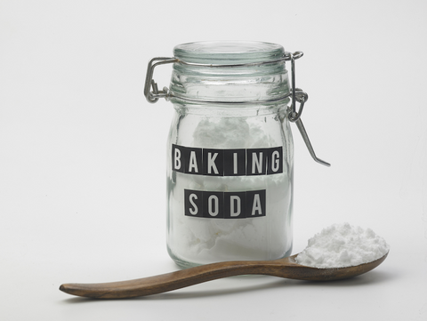 White powder in a jar labelled baking soda and a wooden spoon of powder in front of it