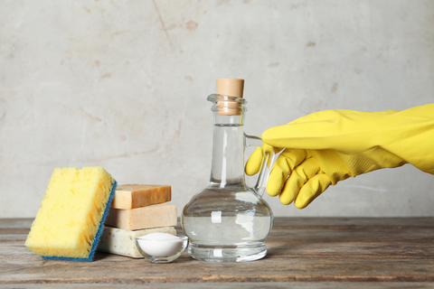 A stoppered flask of colourless liquid with a hand in a yellow glove reaching out to the handle and cleaning supplies on the other side