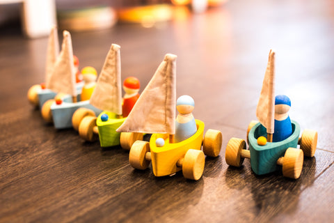 Five wooden boat toys with sails in a row on a parquet floor