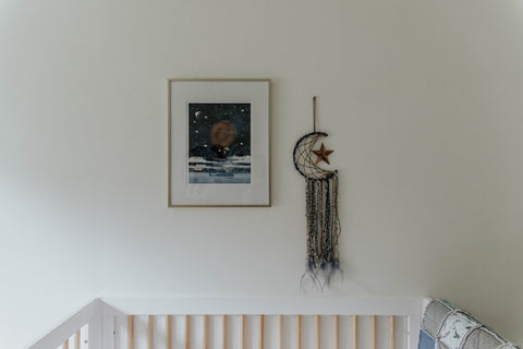 Picture frame and dream catcher hanging above a baby cot