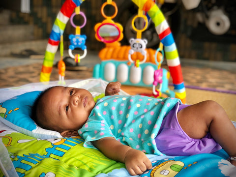 Baby lying down on a play mat with toy in the background
