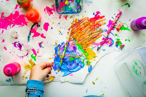 Flat lay of child's artwork with paints on a white background
