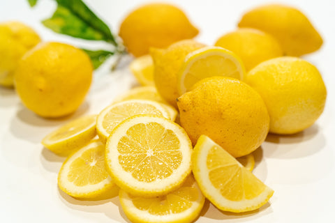 A bunch of lemons, some whole and some sliced