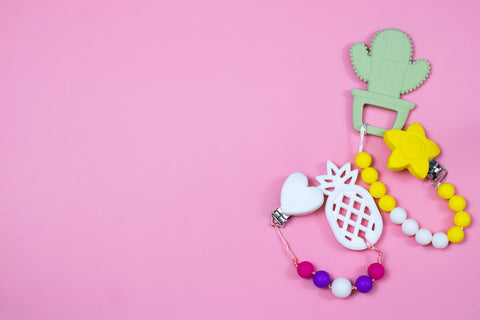 Baby teethers on pink background