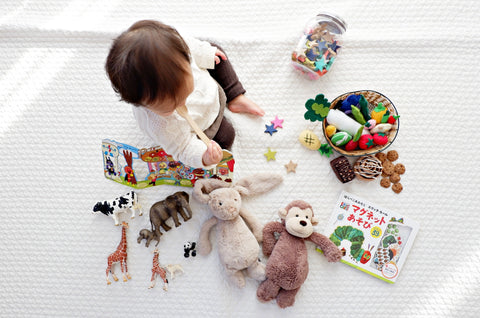 Baby surrounded by toys and books seated on a white mat, taken from above