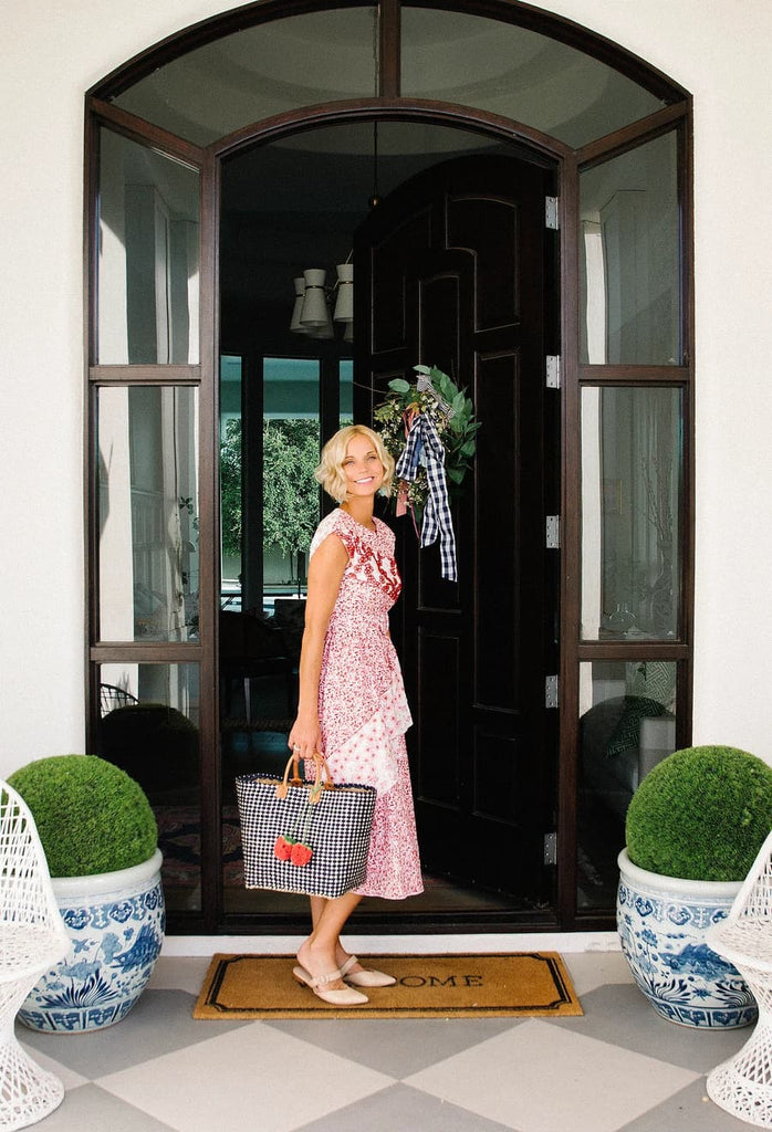 Jen Sumko on a porch in front of a door and holding a purse.