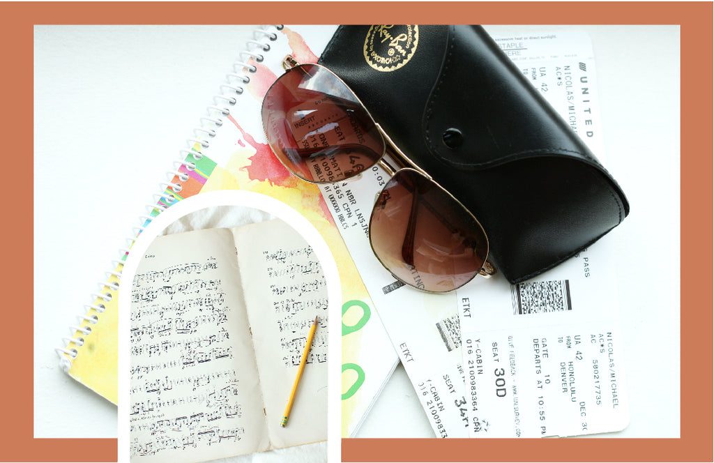 Plane ticket, sunglasses, planner, and a book of music compositions