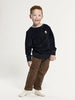Boy with dark blue velvet sweatshirt with small acorn and brown chinos