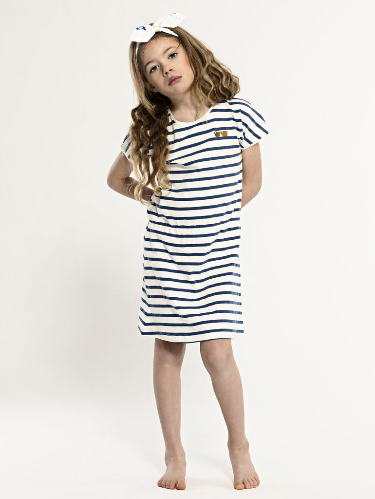 SS19 spring collection from One We Like made of 100% organic cotton. Dress with short sleeves and stripes. Sunglasses at right hand side of chest.