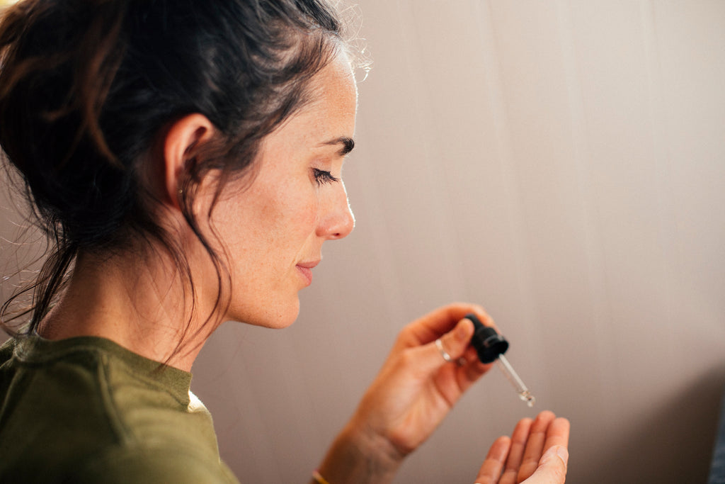 Woman applying kaibae  face oil, wildly luxurious microbiome friendly skin care