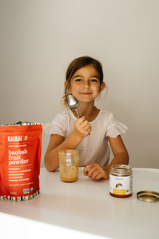 healthy girl eats kaibae organic baobab fruit powder mixed with honey to boost her immune system