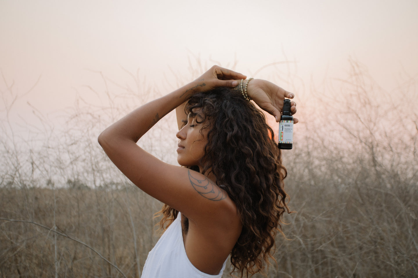 Woman with healthy curly hair stands in the wild and holds a bottle of kaibae pure baobab oil