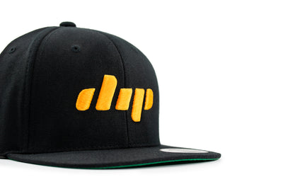 Dip black and yellow flatbill hat profile view close up