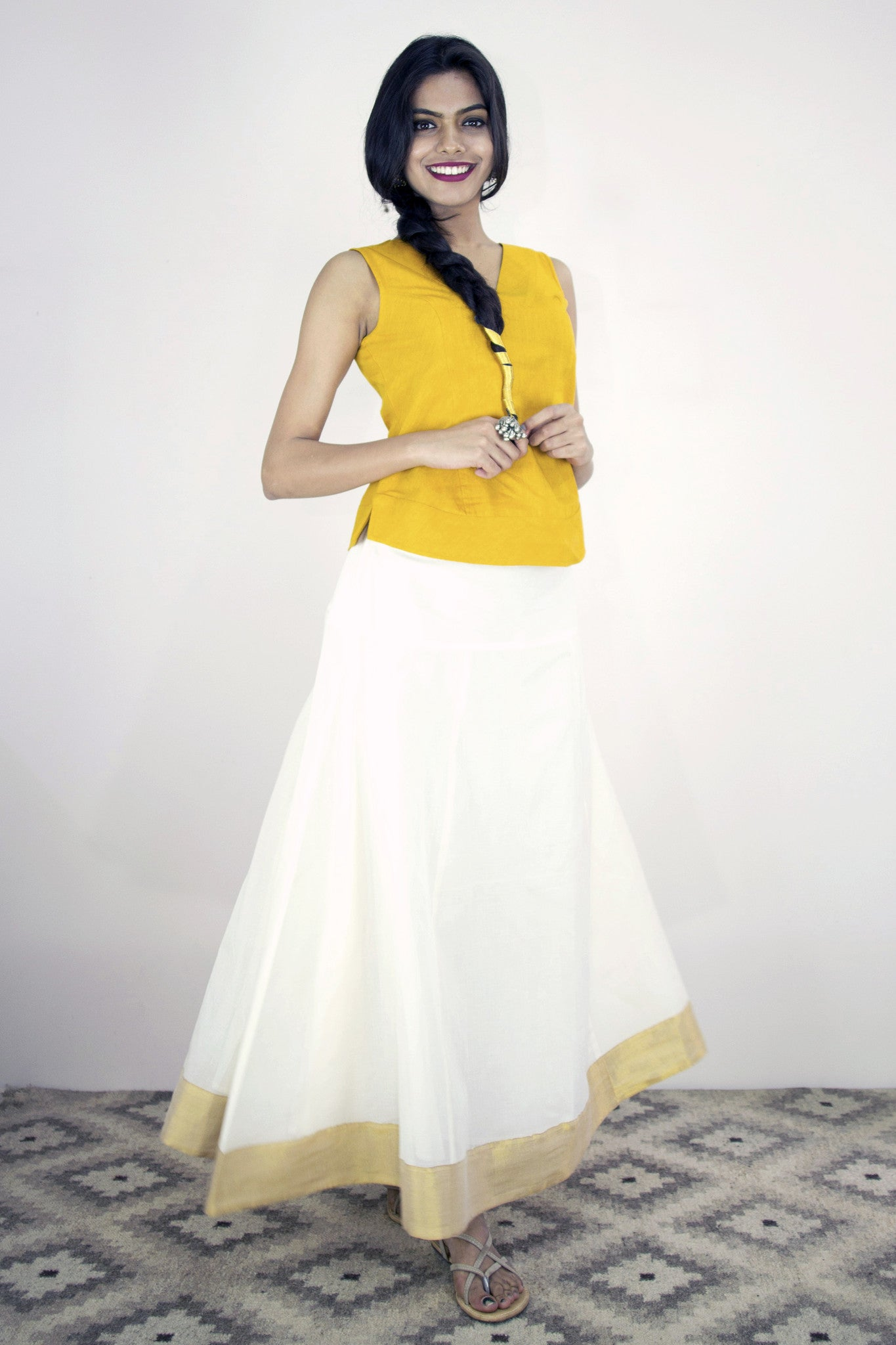 Model is wearing the Twirl skirt in kasavu with a bright yellow top. Button fastening at the side of the waistband. Elastic at the back waistband.With lining