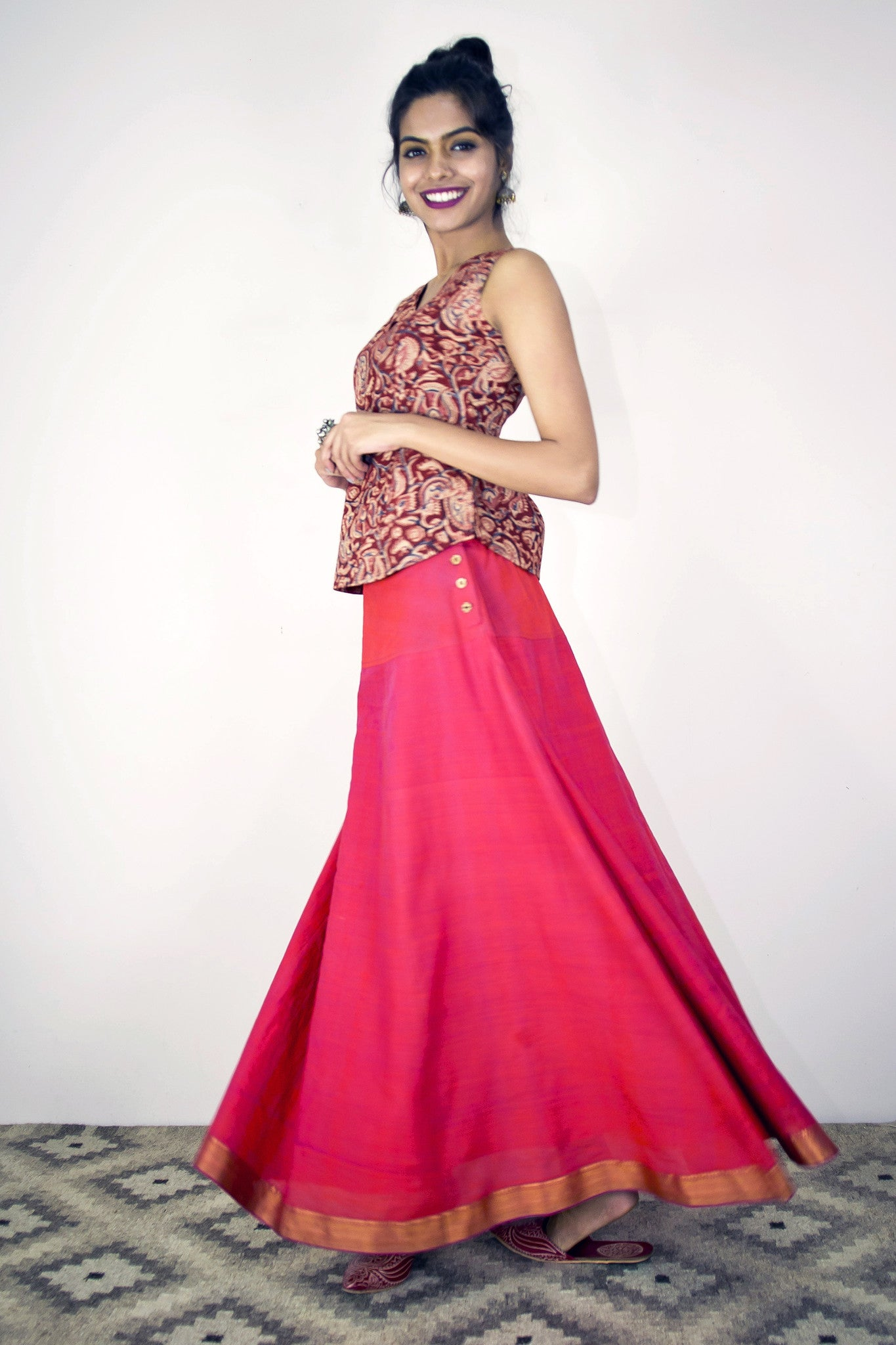 Model is wearing twirl skirt in orange pink mangalgiri paired with gypsy top in maroon kalamkari. With lining.