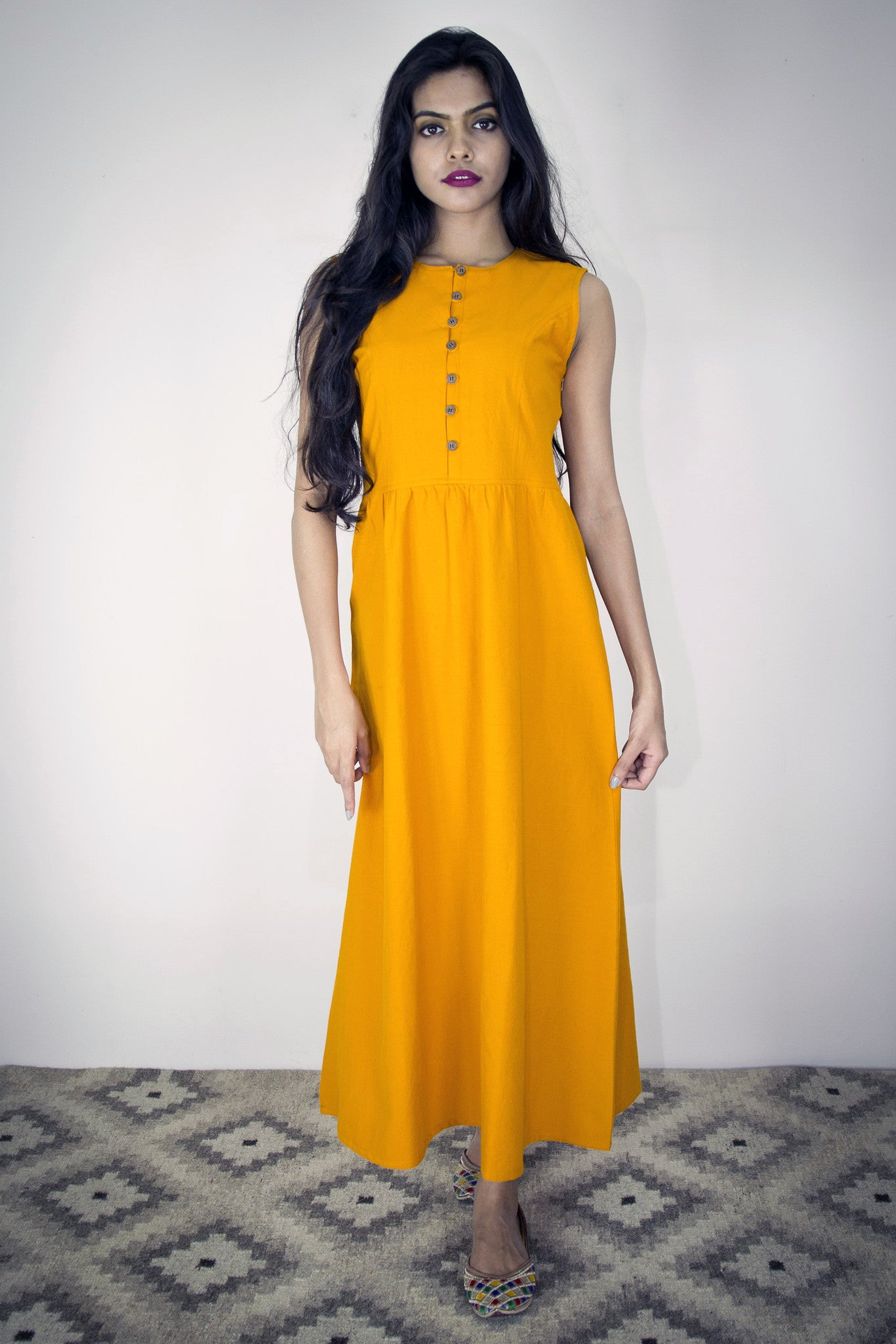 Model is wearing the Karuna maxi dress in haldi cotton. Front button and loop fastening.