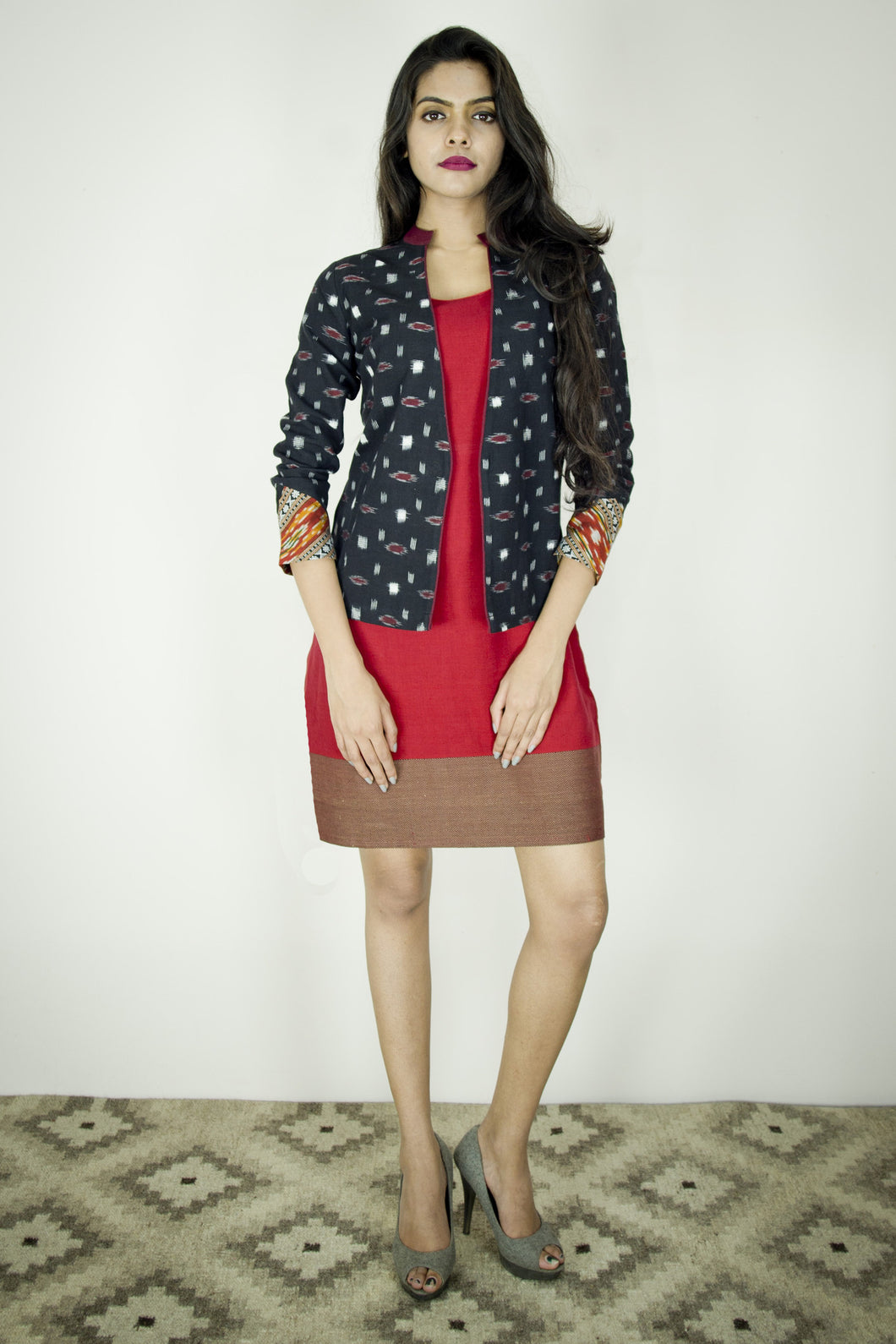 Model is wearing lattice jacket in black maroon white geometric ikat. It is paired with the red bloom dress.