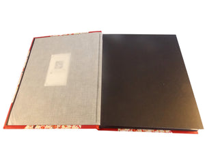 Open view of red leather album showing interleaving tissue