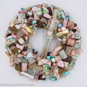 The Cre8ive Art Space Pastel Nutcracker Wreath is full of soft hues that twinkle in the light.   The glittering ribbon choices complement the warn tones. Crafted in the USA