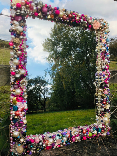 Colour Burst Treasure Mirror made up of baubles, beads, pearls, sparkles and trinkets to create a unique one off mirror perfect for a Salon, Boutique or little girls bedroom.